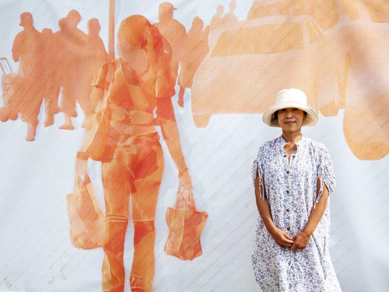 Woman standing in front of outdoor art work