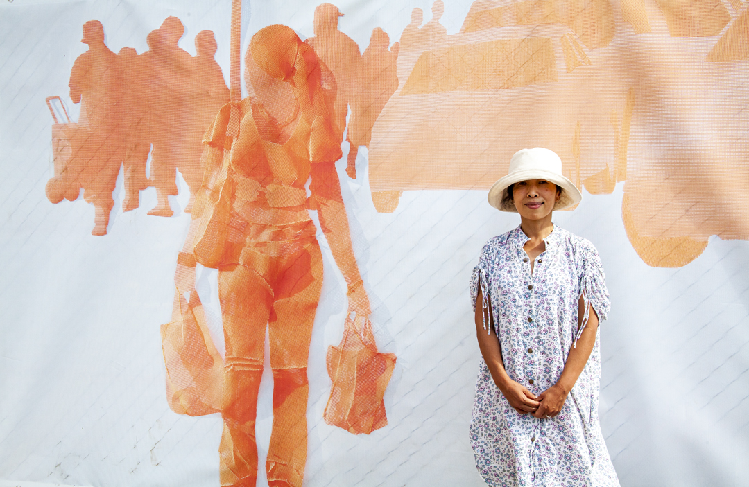 Woman standing in front of outdoor art work