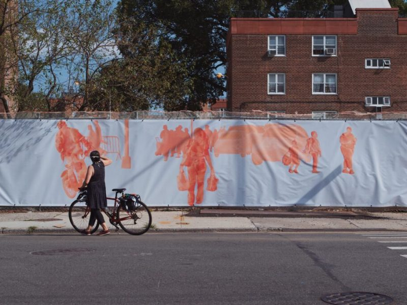 A woman holding her bicycle photographing art