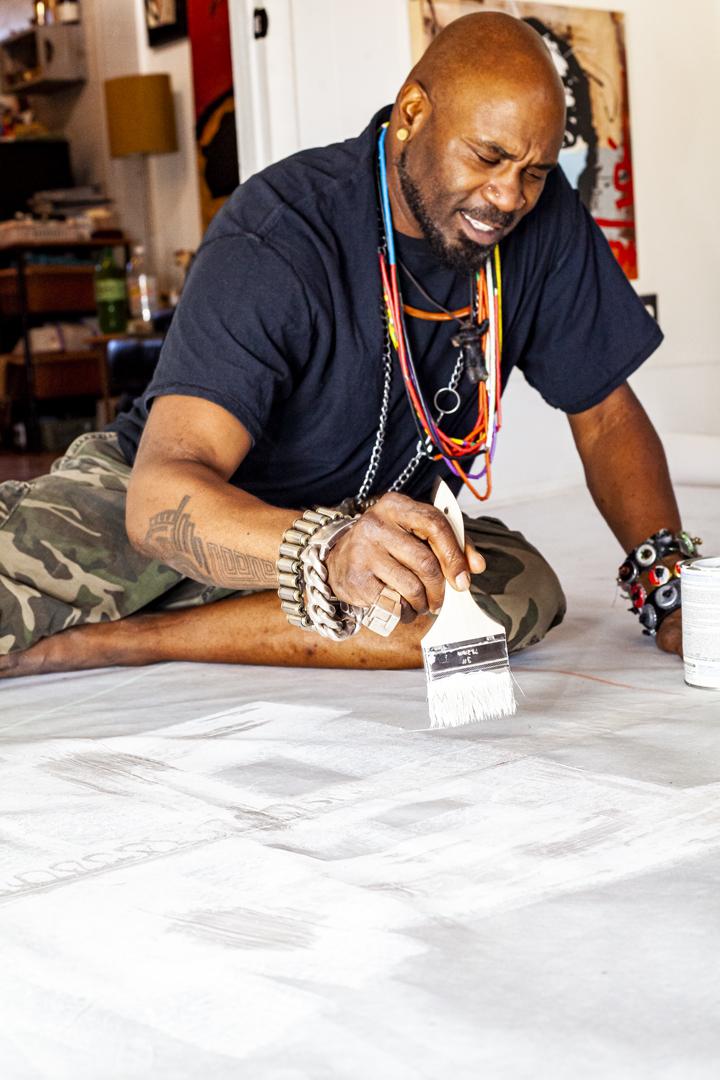 Voodo Fé painting his mural SOAR